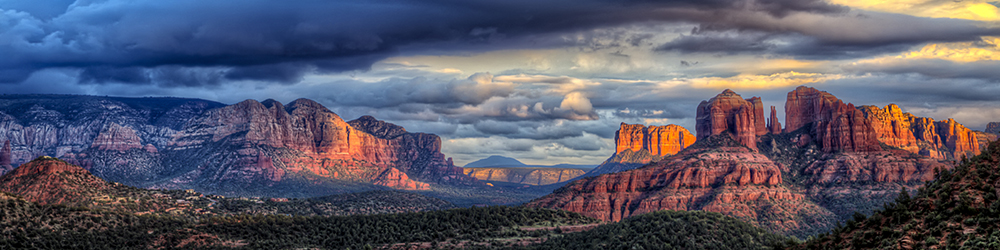 Some dramatic clouds and light from the setting sun on Catherdral Rock in Sedona Arizona.
